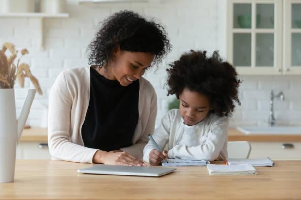 afroamerikanische mutter und kleine tochter studieren online - homeschooling stock-fotos und bilder