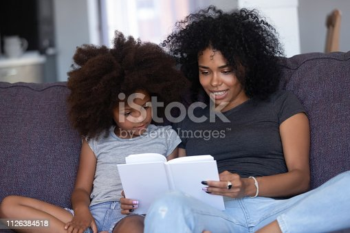 1063760138 istock photo African american mom reading book to little daughter at home 1126384518
