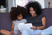 istock African american mom reading book to little daughter at home 1126384518