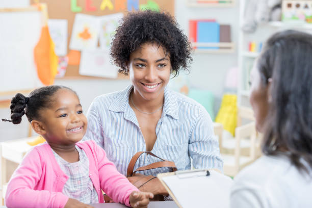 African American mom talks with teacher during conference Young African American mom has a conference with her young daughter's preschool teacher. The little girl is sitting next to her mother. preschool teacher stock pictures, royalty-free photos & images