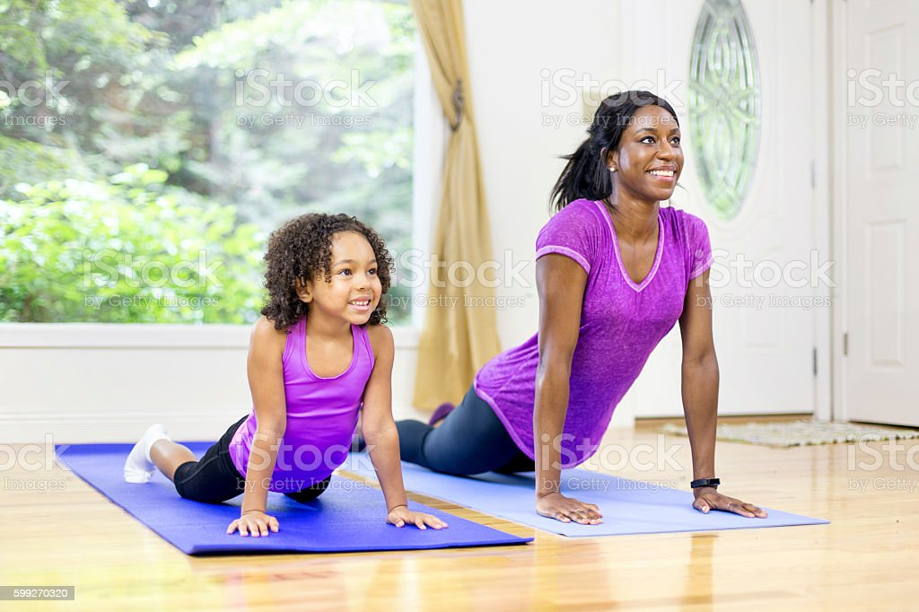 African american mother and daughter doing yoga stock photo