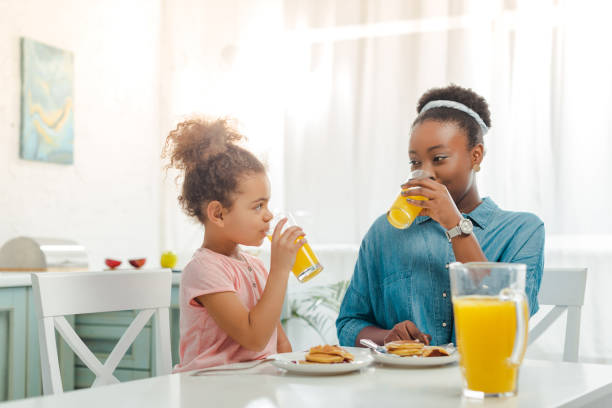 african american mother and daughter drinking orange juice near tasty pancakes stock photo