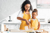 african american mother and daughter preparing dough and whisking eggs in kitchen