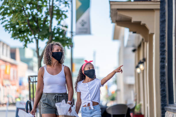African American mother and daughter shopping downtown while wearing masks stock photo