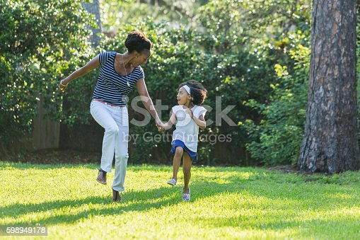 An African American mother with her beautiful young mixed race daughter, holding hands and skipping as they smiling at each other. It is a sunny day in the park or back yard on the grass, with trees and foliage in the background.