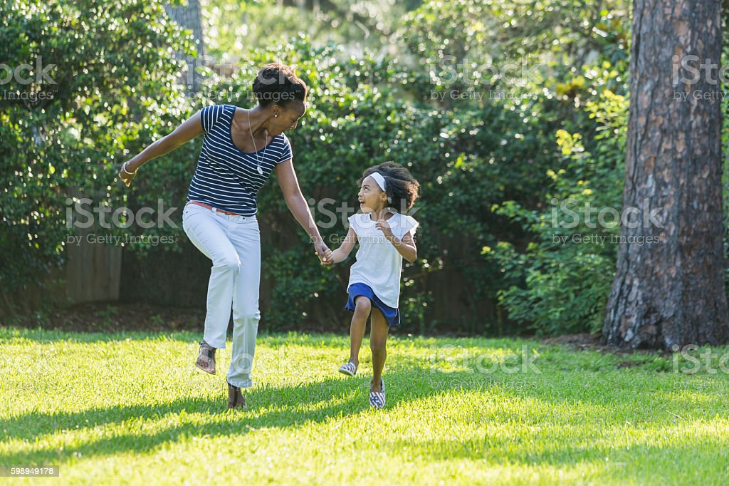 African American mother and daughter skipping, laughing stock photo