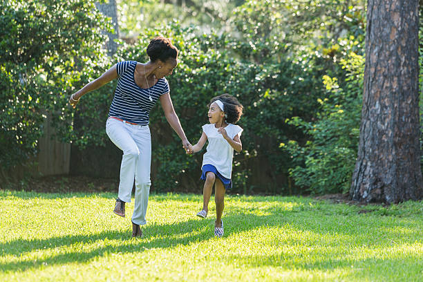 african american mother and daughter skipping, laughing - african youth jumping for joy stock photos and pictures