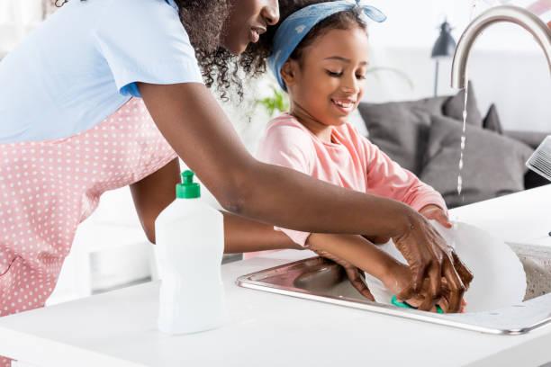 Afro-Amerikaanse moeder en dochter afwassen met afwasmiddel op keuken foto