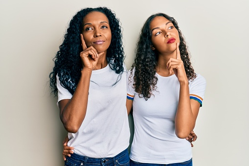 African american mother and daughter wearing casual white tshirt serious face thinking about question with hand on chin, thoughtful about confusing idea