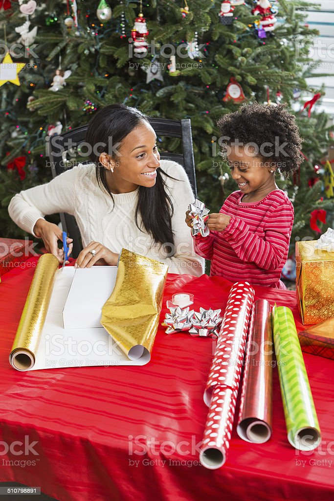 African American mother and daughter wrapping Christmas presents stock photo