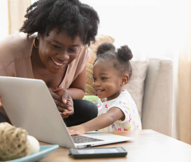 African American mother and her little girl using computer