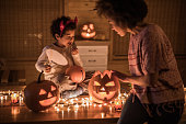 African American single mother decorating pumpkins with her small son on Halloween. Focus is on boy.