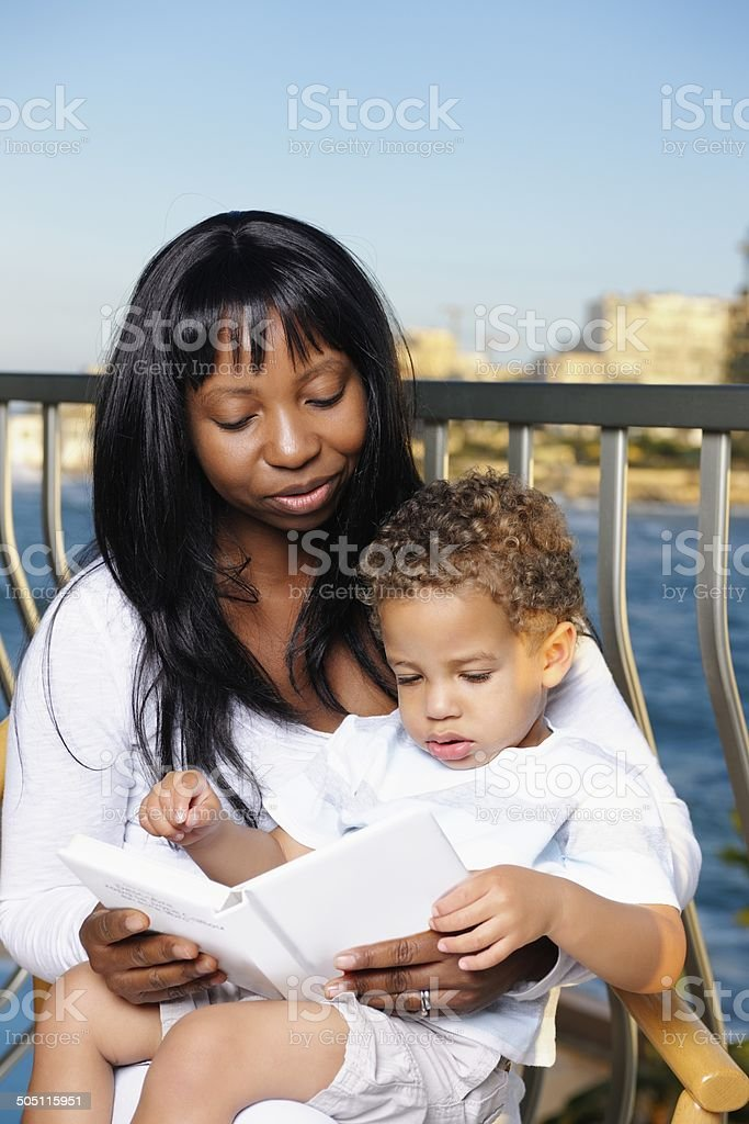 African American Mother And Her Son Reading Whilst On Holiday royalty-free stock photo