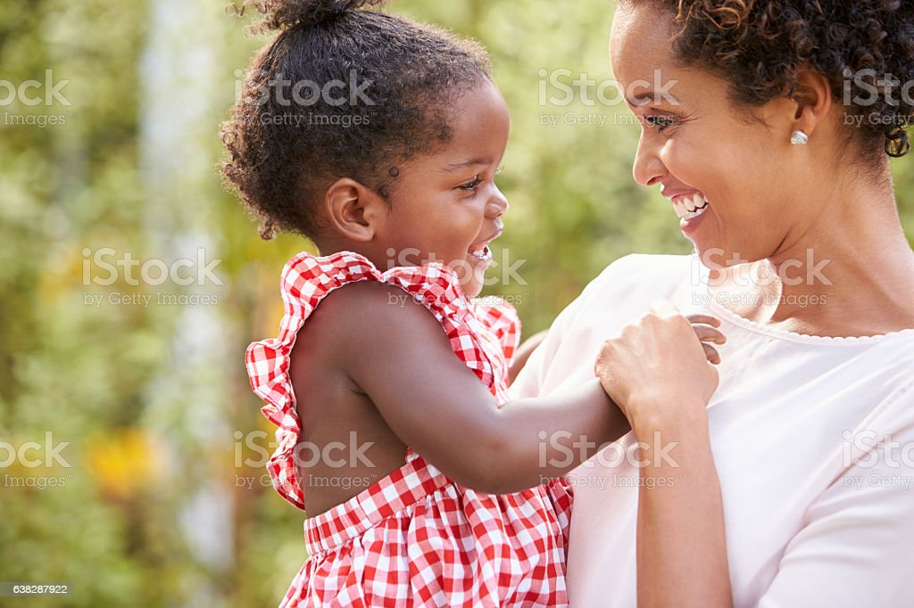 African American mother carries baby daughter and holds hand stock photo