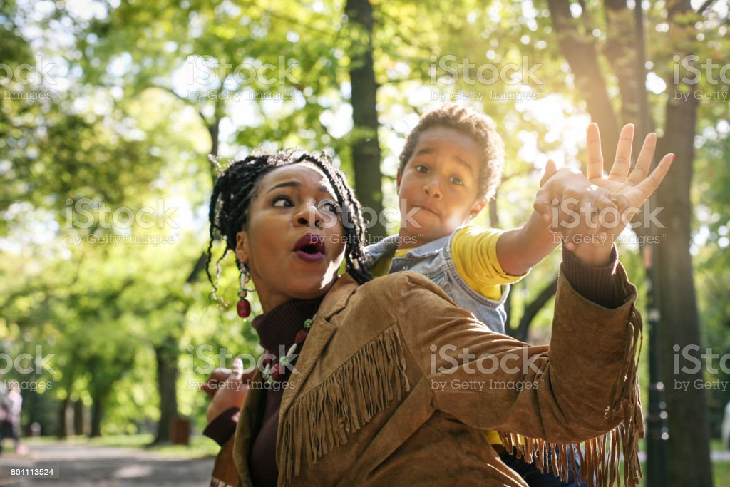 African American mother carrying her little daughter on piggyback. royalty-free stock photo
