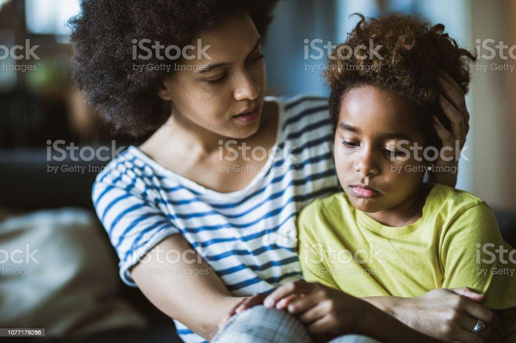 African American mor tröstar henne ledsen flicka hemma. - Royaltyfri Afrikanskt ursprung Bildbanksbilder