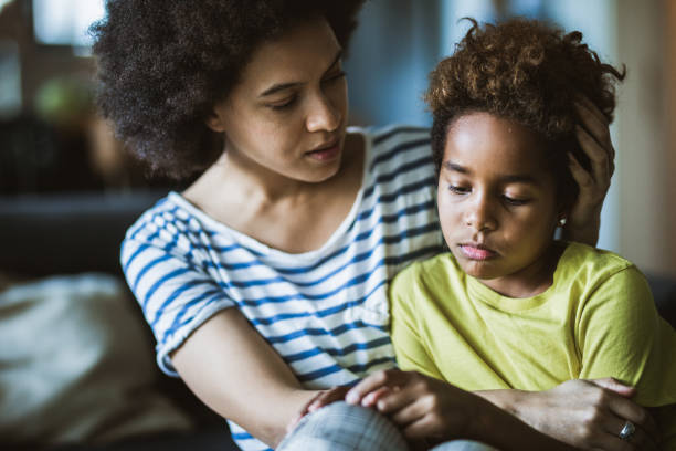 African American mother consoling her sad girl at home. Young black mother taking care of her depressed little daughter at home. sadness stock pictures, royalty-free photos & images