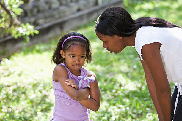 African American mother disciplining daughter African American mother (20s) and daughter (5 years) at the park, little girl frowning. scolding stock pictures, royalty-free photos & images