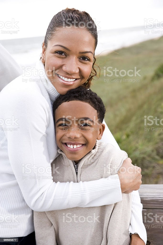 African American mother hugging smiling son at beach stock photo