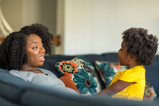 African American mother playing and talking with her daughter. stock photo