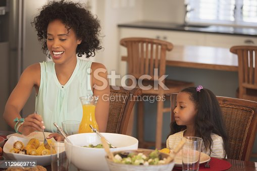 Front view of happy African American serving her African American daughter food at dining table in a comfortable home