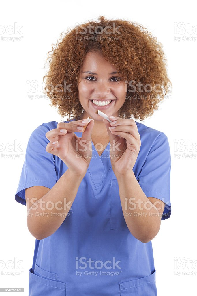 African American nurse holding a broken cigarette stock photo