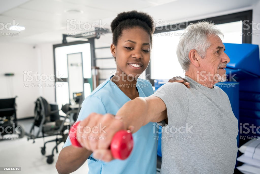 African american occupational therapist helping a senior patient with his shoulder workout stock photo