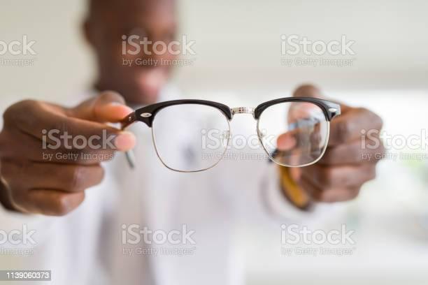 African american optiian man holding and showing glasses lens to at picture id1139060373?b=1&k=6&m=1139060373&s=612x612&h=1e4l8ncqlsdbm2zclgjnpxunigifwrj tbzumn8ih64=
