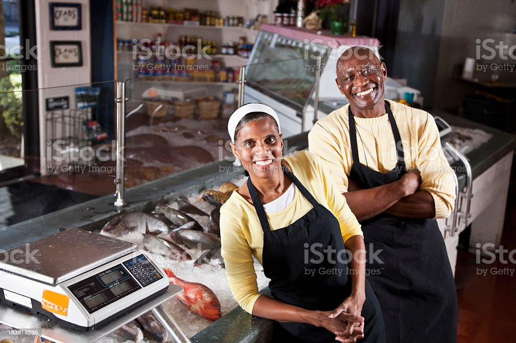 A senior African American couple standing behind the counter of...