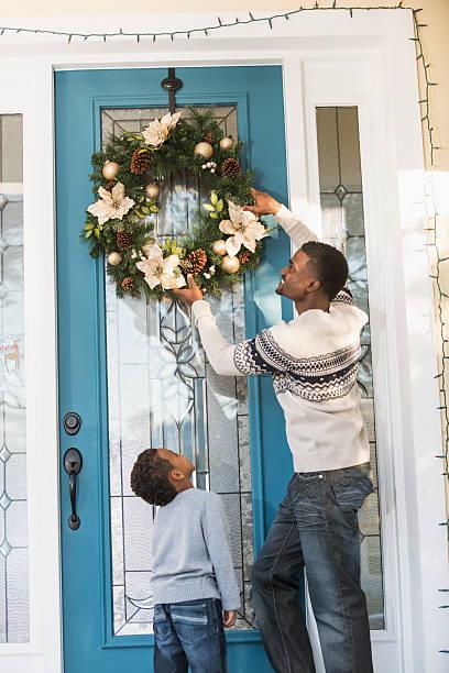 afroamerikanischen eltern und kinder hängen kranz auf der begrüßungsseite - deko hauseingang weihnachten stock-fotos und bilder