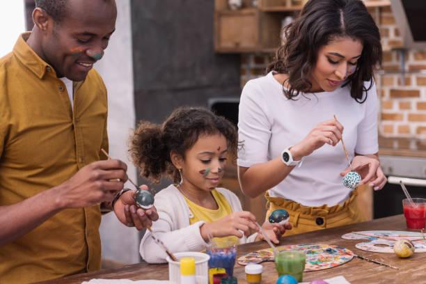 pais americanos africanos e filha pintar ovos de páscoa - familia pascoa - fotografias e filmes do acervo