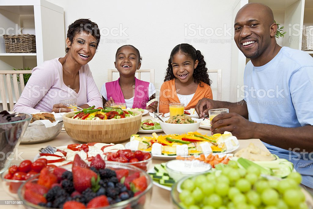 African American Parents Children Family Eating At Dining Table stock photo