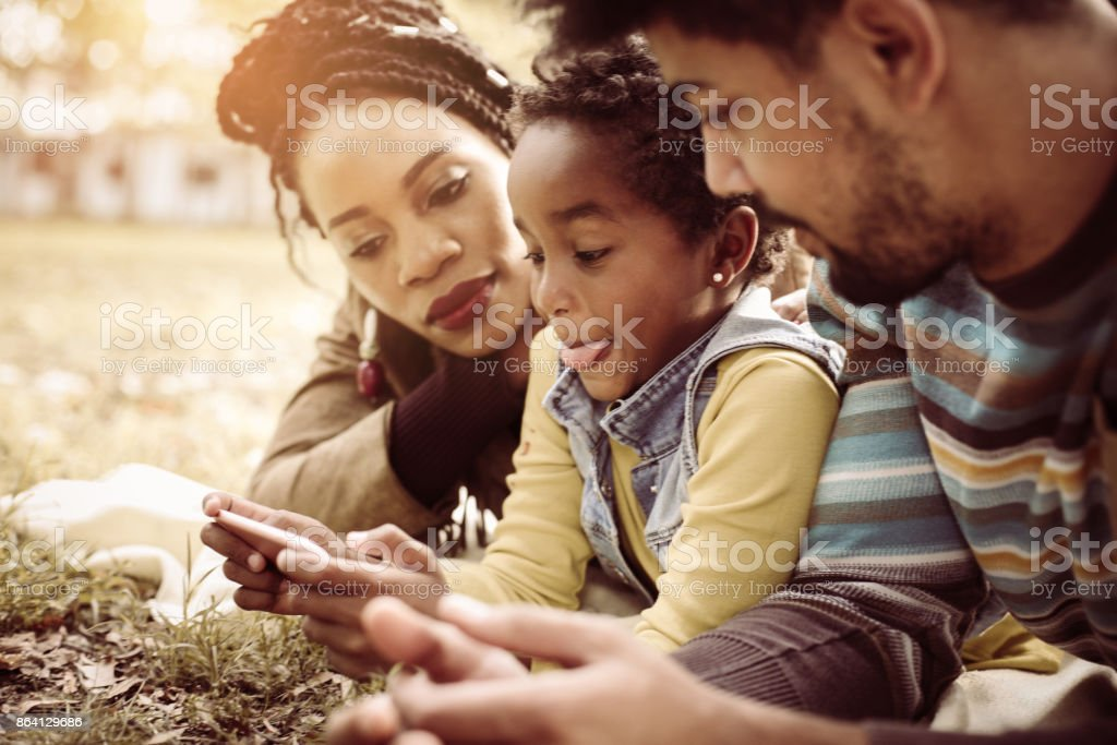 African American parents in park with daughter using mobile phone together. royalty-free stock photo