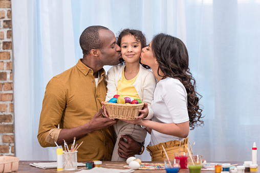 african american parents kissing daughter and holding straw basket with easter eggs