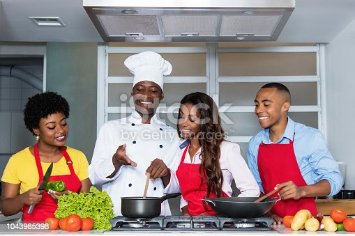African american people learn cooking from chef at kitchen