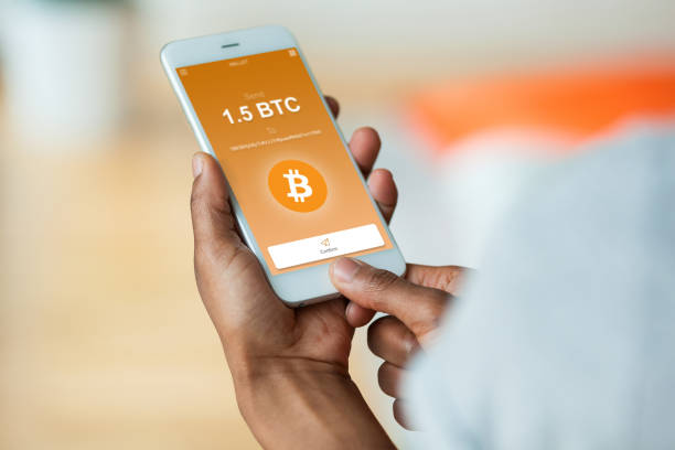 African american person sending a bitcoin btc crypto transaction using  mobile phone wallet - Black people stock photo