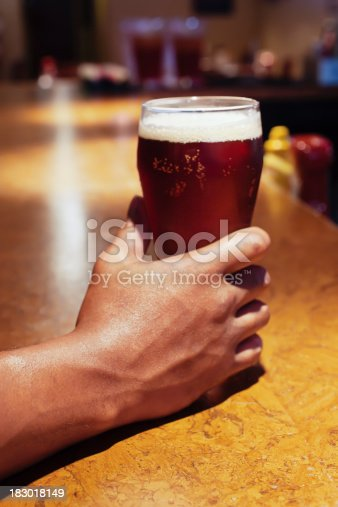istock African American Person's Hand Holding Bar Beer Glass 183018149