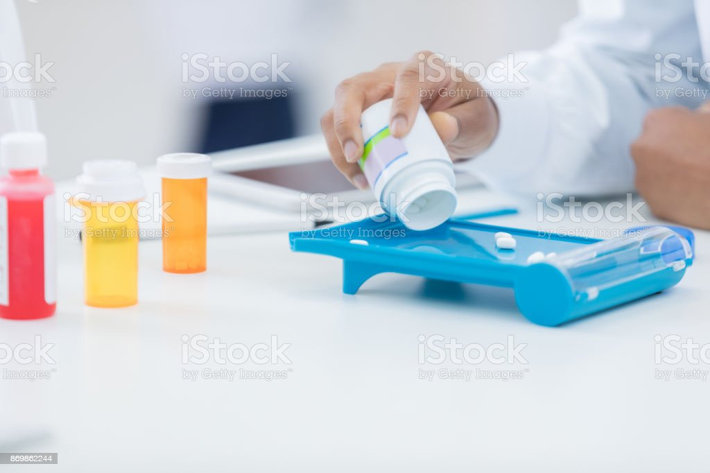 African American pharmacist uses pill counter in a pharmacy stock photo