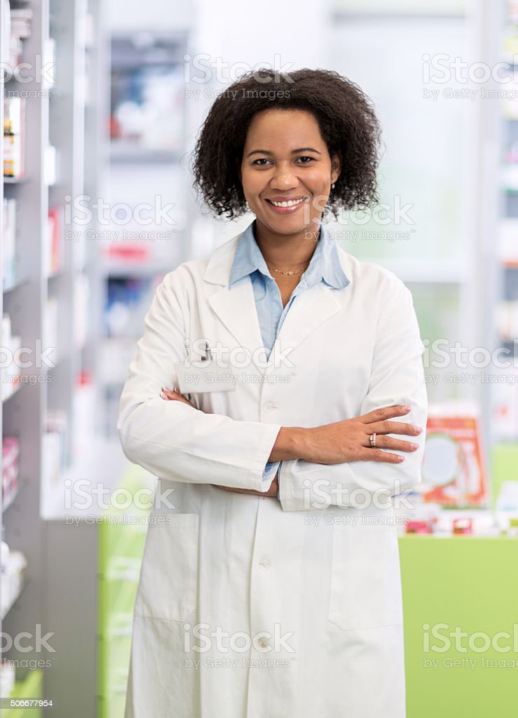African American pharmacist with arms crossed in pharmacy. stock photo