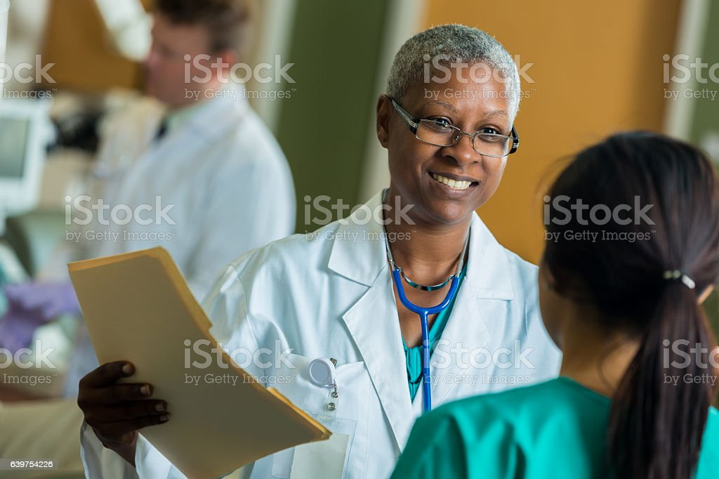 African American phlebotomist talks with nurse stock photo
