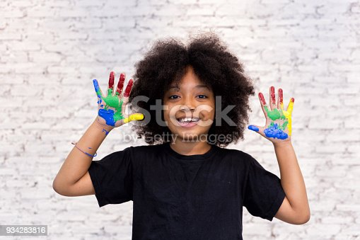 istock African American playful and creative kid getting hands dirty with many colors - in white brick background. 934283816