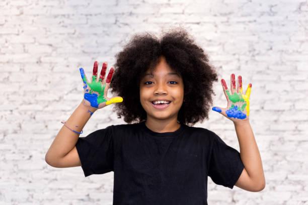 african american spielerische und kreative kind immer hände schmutzig mit vielen farben - in weiße ziegel hintergrund. - interessantes für teenager stock-fotos und bilder