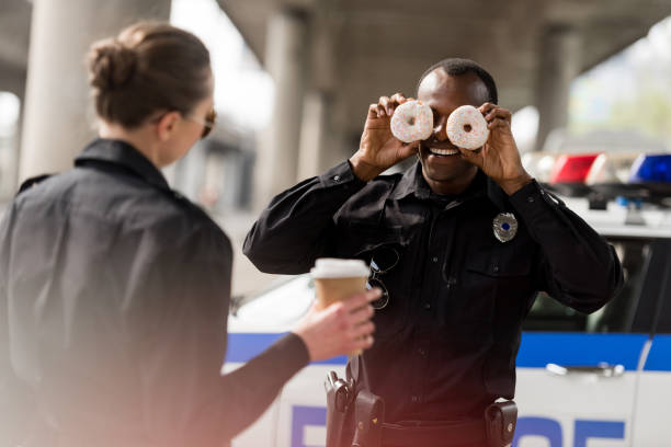 african american police officer pretending doughnuts as his eyes to amuse his partner african american police officer pretending doughnuts as his eyes to amuse his partner amuse stock pictures, royalty-free photos & images
