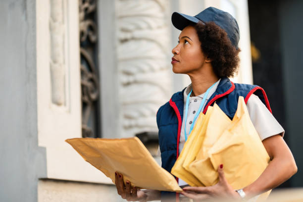 African American postal worker delivering mail in the city. stock photo