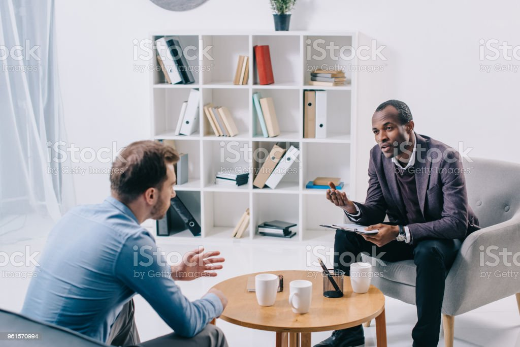 African american psychiatrist talking to young male client stock photo