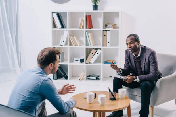 african american psychiatrist talking to young male client - psychiatrist stock photos and pictures