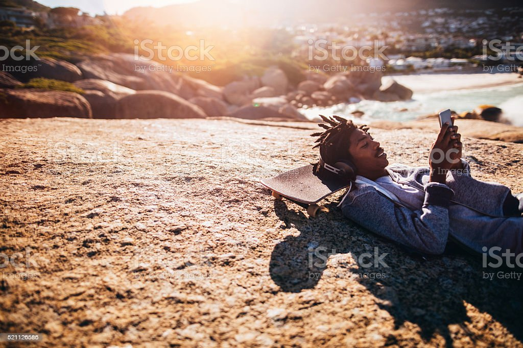 African American Resting and Looking at Smartphone at Seaside stock photo