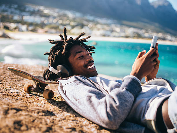 African American Resting, Laughing and Looking at Smartphone at stock photo