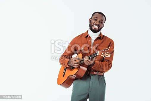 african american retro styled guitarist playing acoustic guitar isolated on white