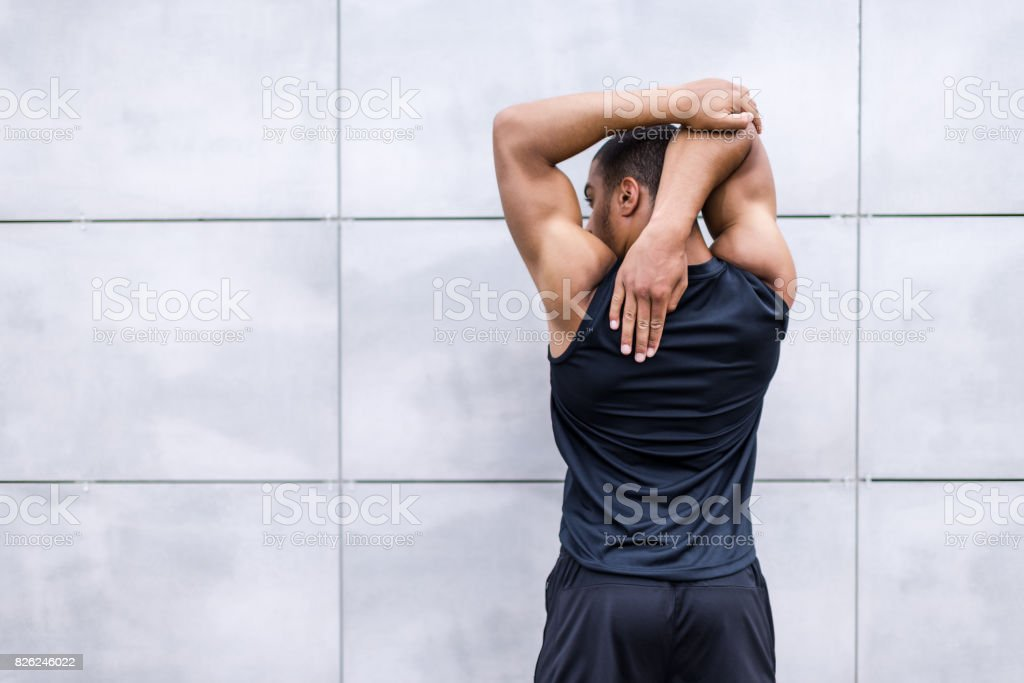 african american runner stretching on street stock photo